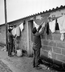 Emigrantes portugueses estendem roupa junto às barracas de um estaleiro de construção civil. Região Parisiense. 1970. Fotografia de Gerald Bloncourt.